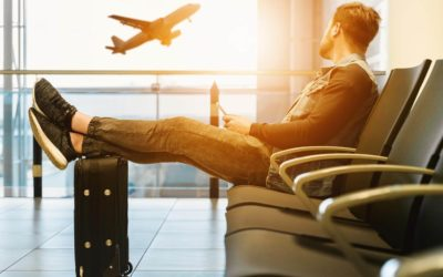 Man watches plane takeoff from gate.